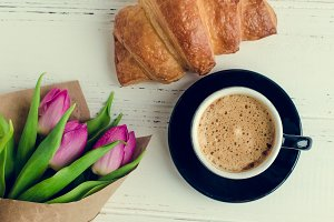 Cup of coffee with bouquet of pink tulips and croissant