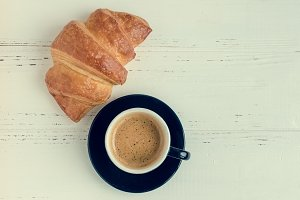 Cup of espresso coffee and fresh baked croissant