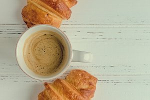 Cup of coffee with milk and fresh baked croissants