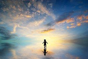 Silhouette of boy walking on water