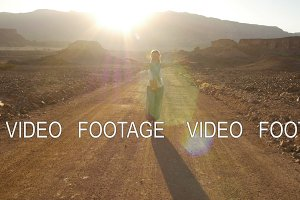 happy young woman walking in desert road on sunset with beautiful sun flare. Timna Park, Israel