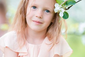 Portrait of adorable little girl in blooming apple tree garden on spring day
