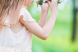 Little beautiful girl enjoying smell of blooming apple tree in a flowering spring garden