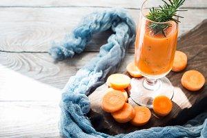 Orange carrot juice on wooden board