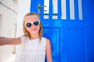 Little adorable girl taking self portrait outdoor background blue door on greek vacation