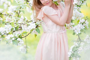 Little adorable girl in blooming cherry tree garden outdoors on Easter eve