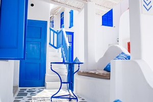 Beautiful terrace with blue chair and table, stairs and flowers. Beautiful terrace exterior with cycladic style.