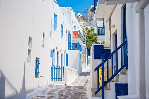 Empty narrow streets of greek island with trees. Beautiful architecture building exterior with cycladic style.