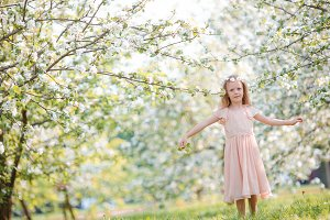 Little girl in blooming cherry tree garden outdoors on Easter eve