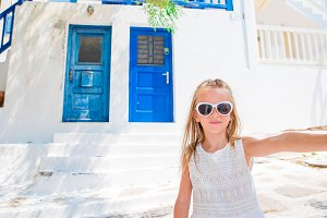 Little adorable girl taking self portrait in Mykonos streets during summer greek vacation