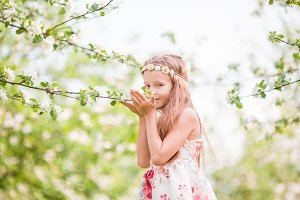 Little beautiful girl enjoying smell in a flowering spring apple garden