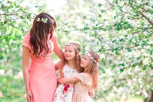 Adorable little girls with young mother in blooming apple garden on Easter