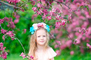 Beautiful little girl in blooming apple tree garden outdoor