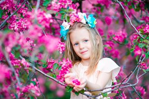 Portrait of adorable little girl in in blooming apple tree garden on spring day
