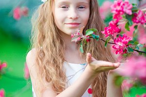 Adorable little girl enjoying smell in a flowering spring garden