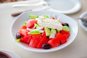 Traditional fresh greek salad, frappe and brusketa served for lunch at outdoor cafe