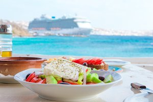 Traditional lunch with delicious fresh greek salad and brusketa served for lunch at outdoor cafe with view on the sea