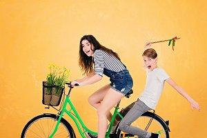Girl and boy on green bike.