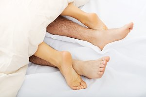 Couple's feet in bed.