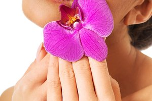 Woman with purple orchid and closed eyes
