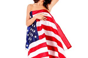 Beautiful brunette woman wrapped into American flag.