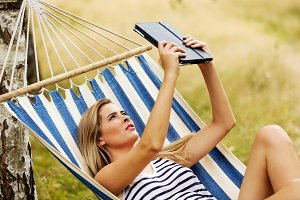 Young woman with tablet on the hammock