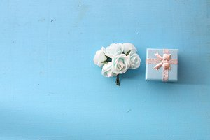 roses and gift box on a blue background