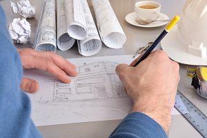 drawing a house on his office desk