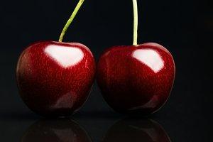 Two juicy fresh cherries on black background