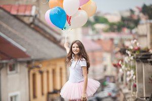Girl with colorful latex balloons