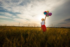 Girl with balloons in wheat field