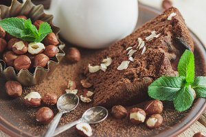 Piece of chocolate cake, mint leaves, hazelnuts, and jar with milk