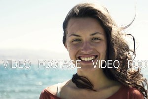 young woman with beautiful smile and hair standing in wind against sea landscape and look at camera