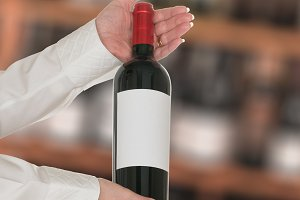 Sommelier offering bottle of red wine to customer