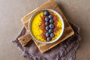 yellow smoothie. Soup with berries blueberry. Bread, Gray Background.