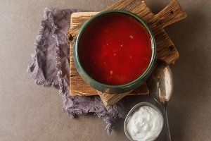 Borscht. Traditional Russian dish, a soup with beets and potatoes. Dark background.
