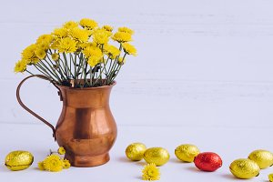 Easter composition with chocolate eggs and flowers