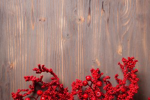 Holly berry twigs on wood wall