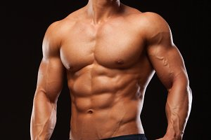 Fitness muscular man is posing and showing his torso with six pack abs. isolated on black background with copyspace