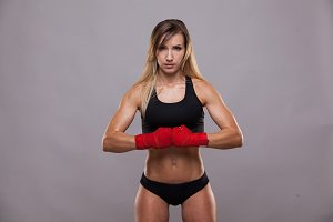athletic girl posing in red bandages, isolated on the grey background boxing fighter kickbox