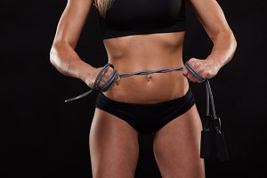 Beautiful fitness woman is holding a skipping rope, close view. Sporty girl showing her well trained body. isolated on dark background with copyspace