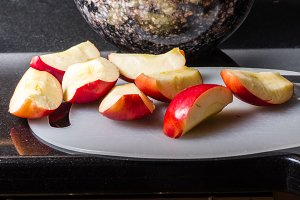 Sliced red apples on cutting board with bowl