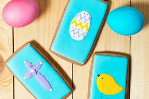 Easter homemade gingerbread cookies and eggs on wooden table