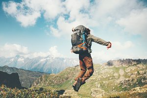 Man jumping with heavy backpack
