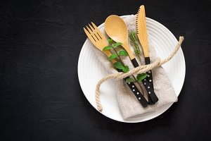 Natural table setting with bamboo knife fork and spoon on a blac