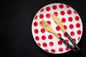 table setting with a bamboo knife, fork and plate with polka dot