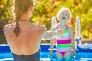 smiling healthy mother and child in swimming pool playing