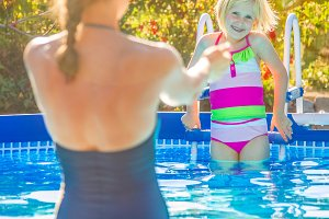 healthy mother and child in swimsuit in swimming pool playing