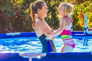 happy healthy mother and child in swimming pool playing