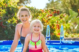 happy active mother and daughter standing in swimming pool